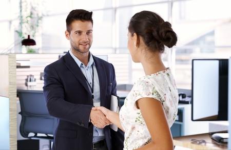 若いビジネスマンとビジネスウーマン握手します。
