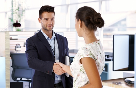Young businessman and businesswoman shaking hands. Imagens