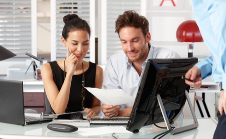 co work: Happy young businesspeople working together in office.