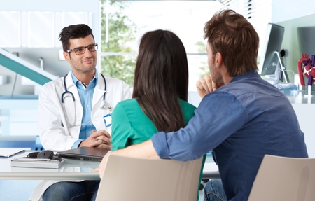 clinician: Male doctor consulting with young couple in doctors room.
