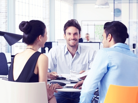 teamworking: Happy young businesspeople working in team, sitting at desk. Stock Photo