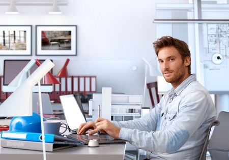 computer engineer: Handsome young architect sitting at desk, using drawing pad, working, looking at camera.