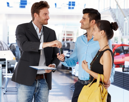 car keys: Young couple receiving car keys from agent in car showroom. Stock Photo