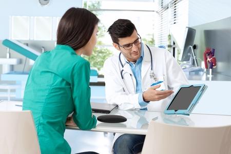 Doctor overleg met vrouwelijke patiënt, de presentatie van de resultaten op de tablet-computer, zittend aan een bureau. Stockfoto