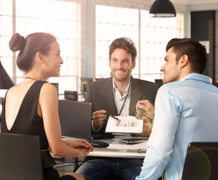 co work: Young couple sitting at desk with financial advisor, discussing charts.