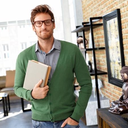 Portrait de jeune homme tenant des livres, en regardant la caméra.