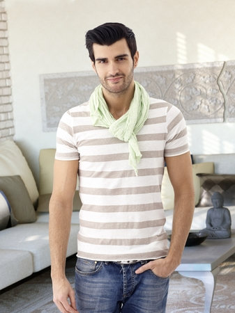 bristly: Casual young man standing at home hand in pocket, smiling, looking at camera. Stock Photo