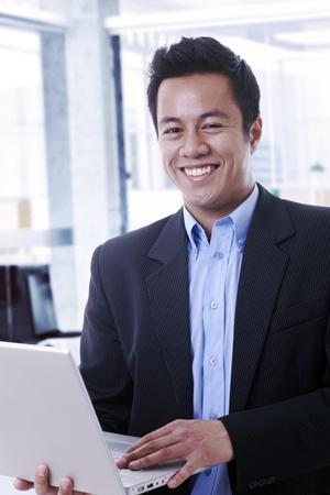 open collar: Portrait of happy smiling asian businessman holding laptop computer.