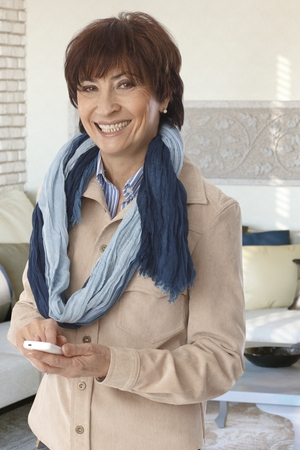 Portrait of stylish mature woman using mobilephone, smiling, looking at camera. photo