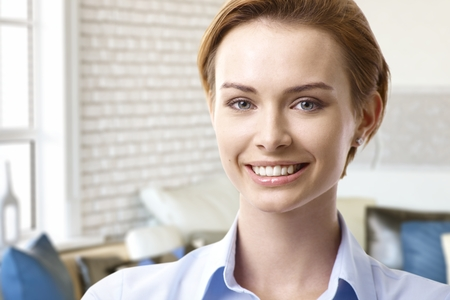 gingerish: Close-up portrait of attractive young woman smiling happy, looking at camera.