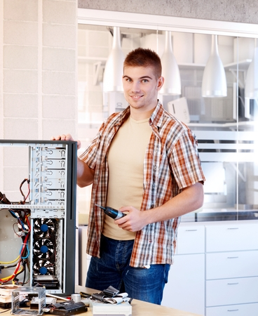 stockphoto: Young mechanic working, reparing computer.