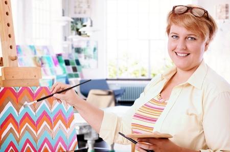 mujer sola: Feliz pintura mujer gorda en casa, sonriendo, mirando a la cámara. Foto de archivo