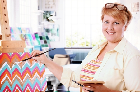 Happy fat woman painting at home, smiling, looking at camera.