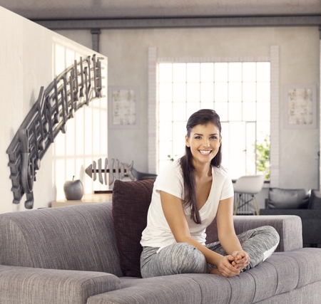 tailor seat: Happy young woman sitting on sofa in living room in tailor seat, smiling, looking at camera.