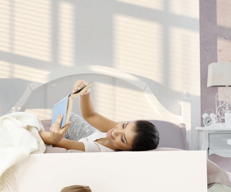 stockphoto: Young woman lying in bed, reading book, smiling.