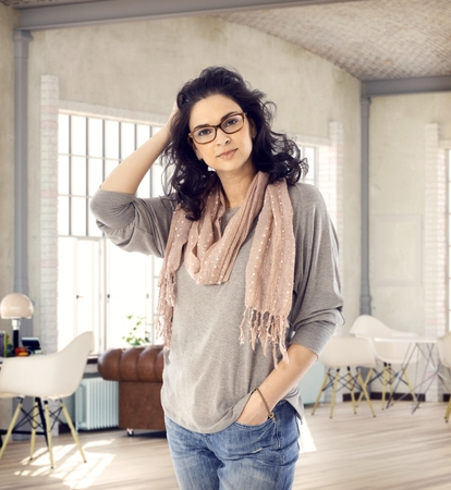 mid adult women: Stylish young woman standing in loft apartment, looking at camera, smiling hand in hair.