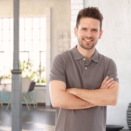 stockphoto: Happy casual man standing arms crossed at home, looking at camera.