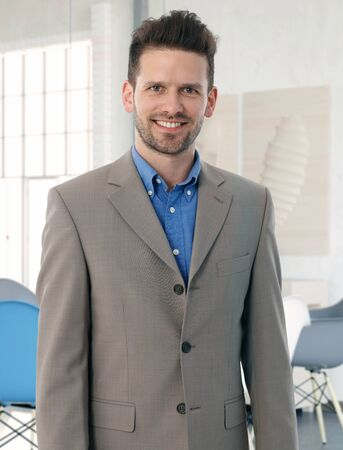 stockphoto: Smiling businessman in suit, looking at camera.