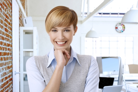 gingerish: Portrait of happy smiling young attractive woman with short hair, hand on chin, looking at camera. Stock Photo