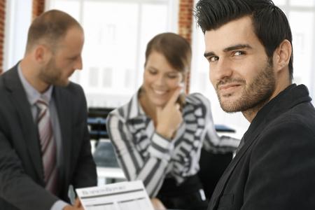 comunicarse: Retrato de joven apuesto hombre de negocios mirando a la cámara, colegas que trabajan en segundo plano.