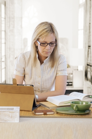 40 45 years: Blonde woman sitting at desk, reading book, using tablet computer.