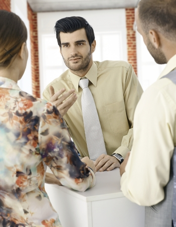 co work: Portrait of young businessman talking to colleagues. Stock Photo