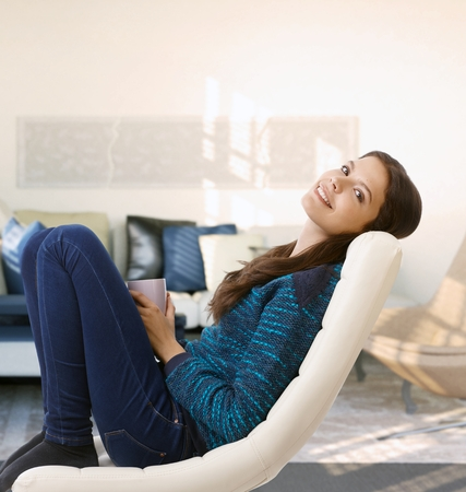 Happy young woman sitting in comfy chair, relaxing at home, drinking tea. Stockfoto