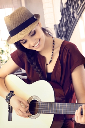 young woman smiling: Closeup portrait of young woman playing the guitar, smiling happy.