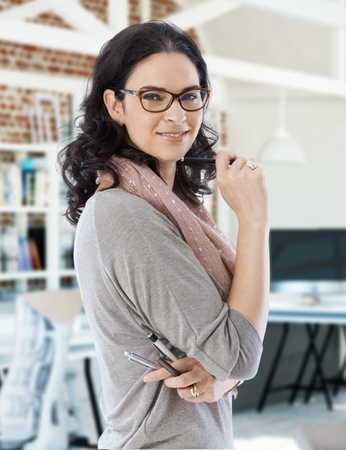 woman  glasses: Young businesswoman smiling, holding pens, looking at camera. Stock Photo