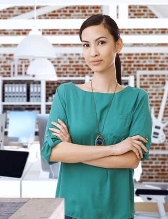 executive woman: Portrait of confident Asian businesswoman standing arms crossed.
