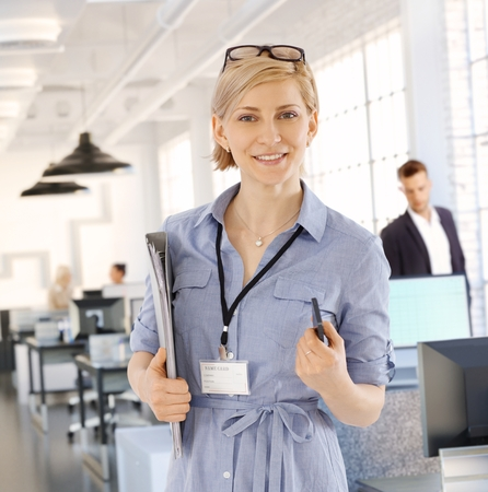Portrait of smiling blonde businesswoman holding files, looking at camera. photo
