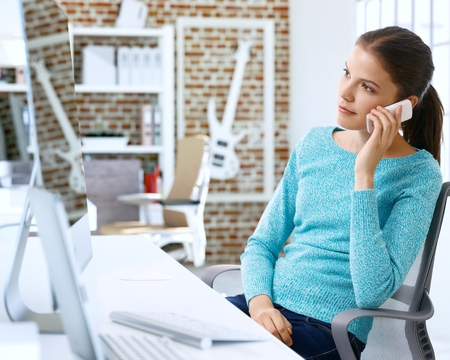 18 20 years: Young woman sitting at desk, talking on mobilephone. Stock Photo