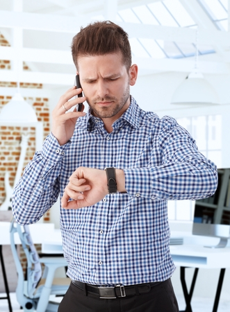 impatient: Businessman standing at office, looking at wristwatch anxious, using mobile.