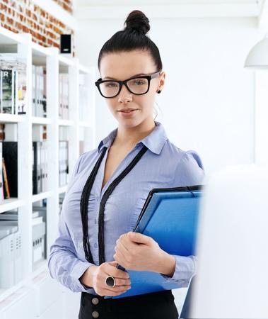 bollos: Retrato de la secretaria bastante joven que sostiene carpetas, mirando a la cámara. Foto de archivo