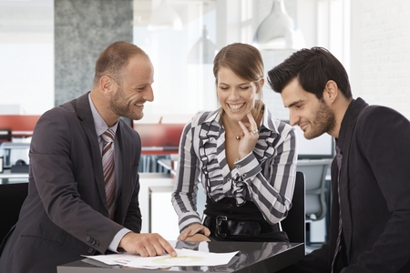 co work: Happy businessteam sitting around table, working together, smiling. Stock Photo