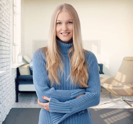 blue eye: Happy blonde woman smiling arms crossed at stylish home.