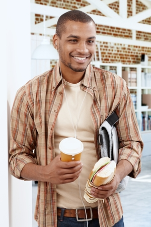 black business men: Happy smiling young black man listening to music on earbuds, holding coffee and sandwich.