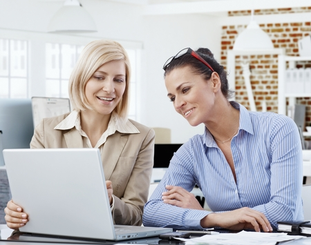 co work: Happy businesswomen working together, using laptop, smiling.