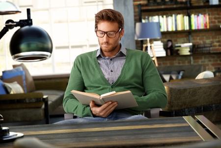 personas leyendo: Libro de lectura de joven hombre en su casa a la antigua.