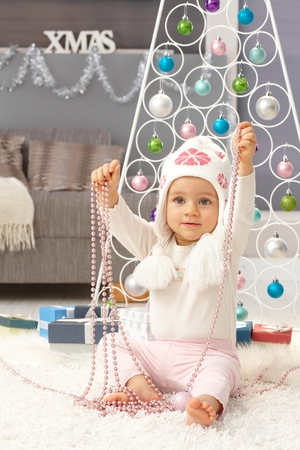 Cute little girl playing with ornaments at christmas time.