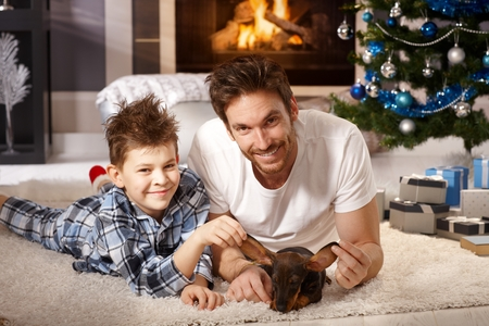 nighty: Young father and son lying on floor, playing with puppy received for christmas.