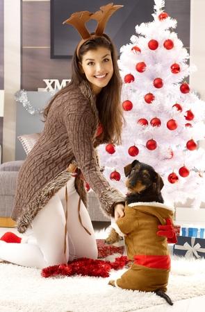 mujer rodillas: Feliz mujer de rodillas por árboles de Navidad, llevaba cornamenta de reno, sonriendo, jugando con el perro. Foto de archivo