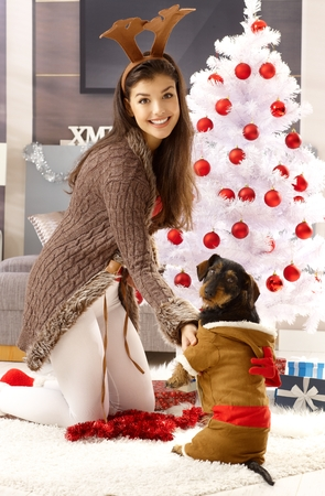 young tree: Happy woman kneeling by christmas tree, wearing reindeer antler, smiling, playing with dog.
