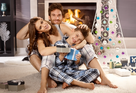 christmas morning: Happy attractive young family loving, hugging and having fun at christmas morning in pajamas on floor by christmas tree.
