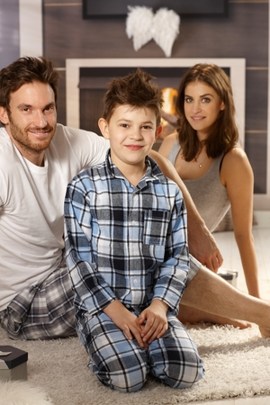 nighty: Young family sitting on floor in pajamas, smiling.