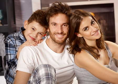 nighty: Closeup portrait of happy young family with little boy, smiling, looking at camera.