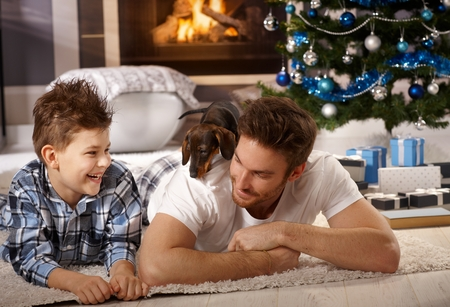 Father and son playing with puppy at christmas time.