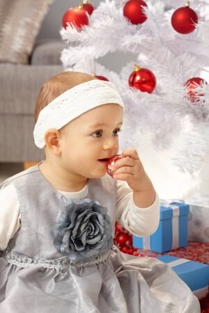 fancy sweet box: Little girl sitting under Christmas tree in elegant dress. Stock Photo