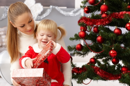 young tree: Mother and daughter sitting by christmas tree, opening presents.