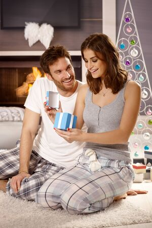 young tree: Young couple opening presents at christmas morning in pajamas on floor. Stock Photo